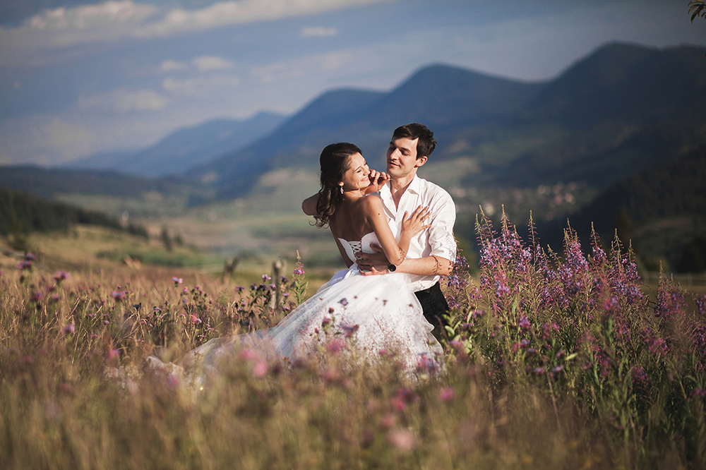 Romantic fairytale couple newlyweds kissing and embracing on a background of mountains.